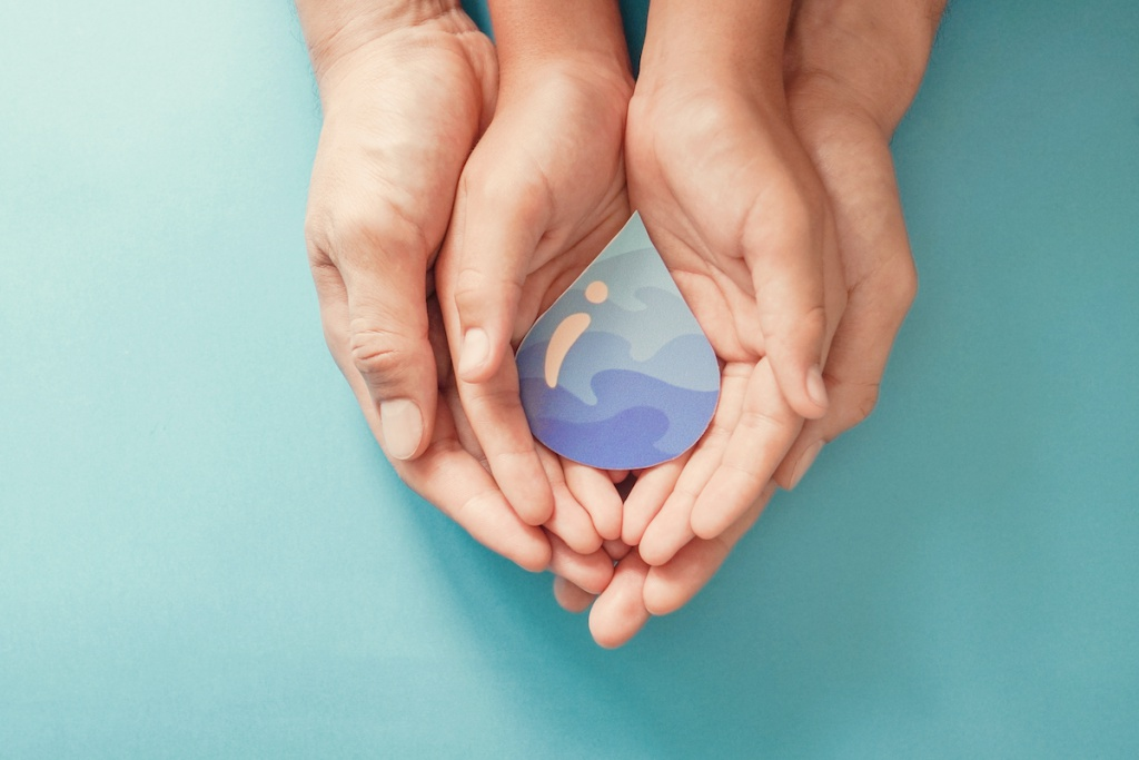 Adult and child hands holding paper cut water drop, World Water Day,  Clean water and sanitation, CSR, save water,  ecology concept